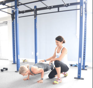 personal trainer guiding middle aged women doing pushups